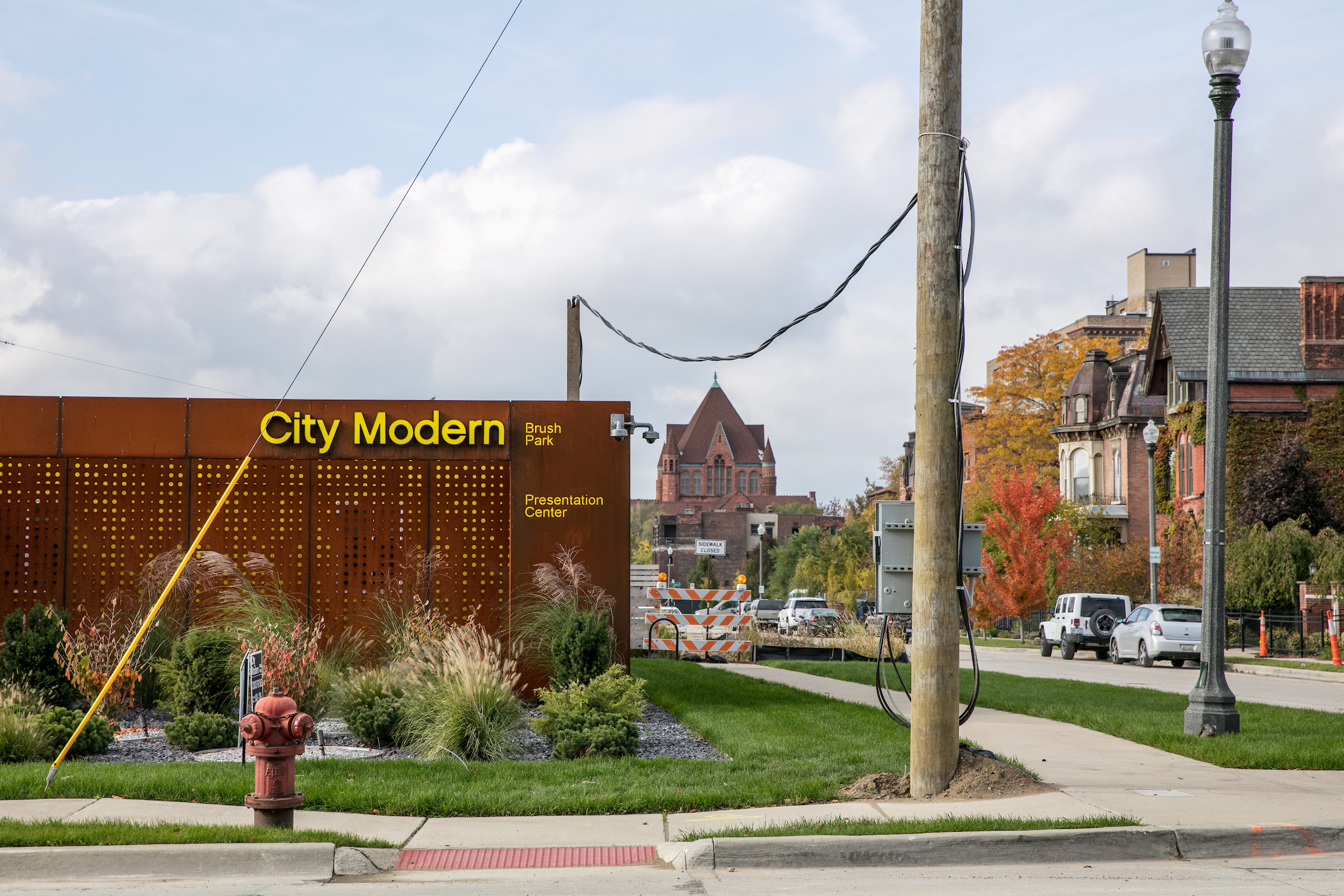 A yellow sign on a rust-colored building advertising City Modern in Brush Park on a sunny day in Detroit.