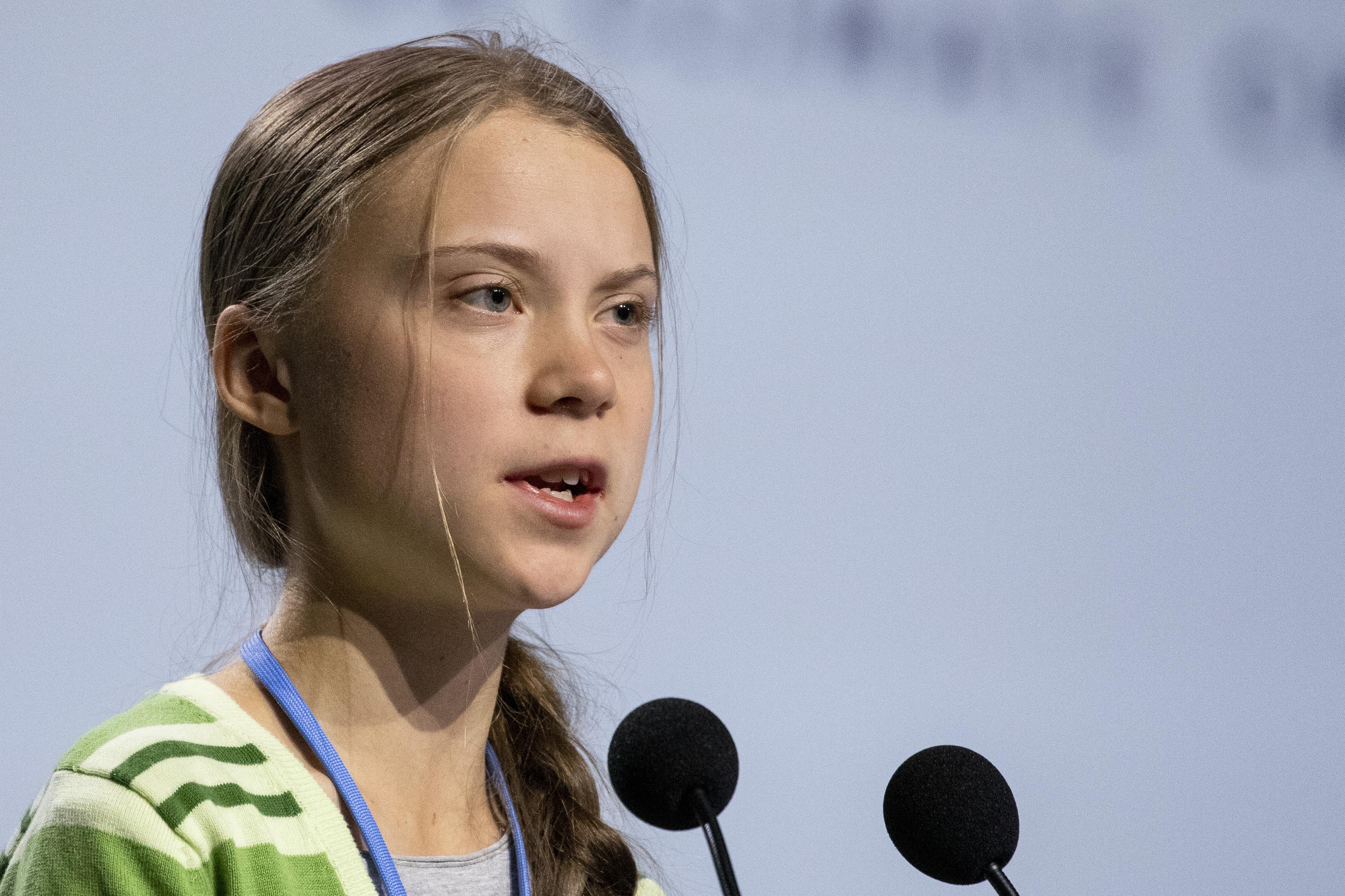 Greta Thunberg speaks into a microphone.