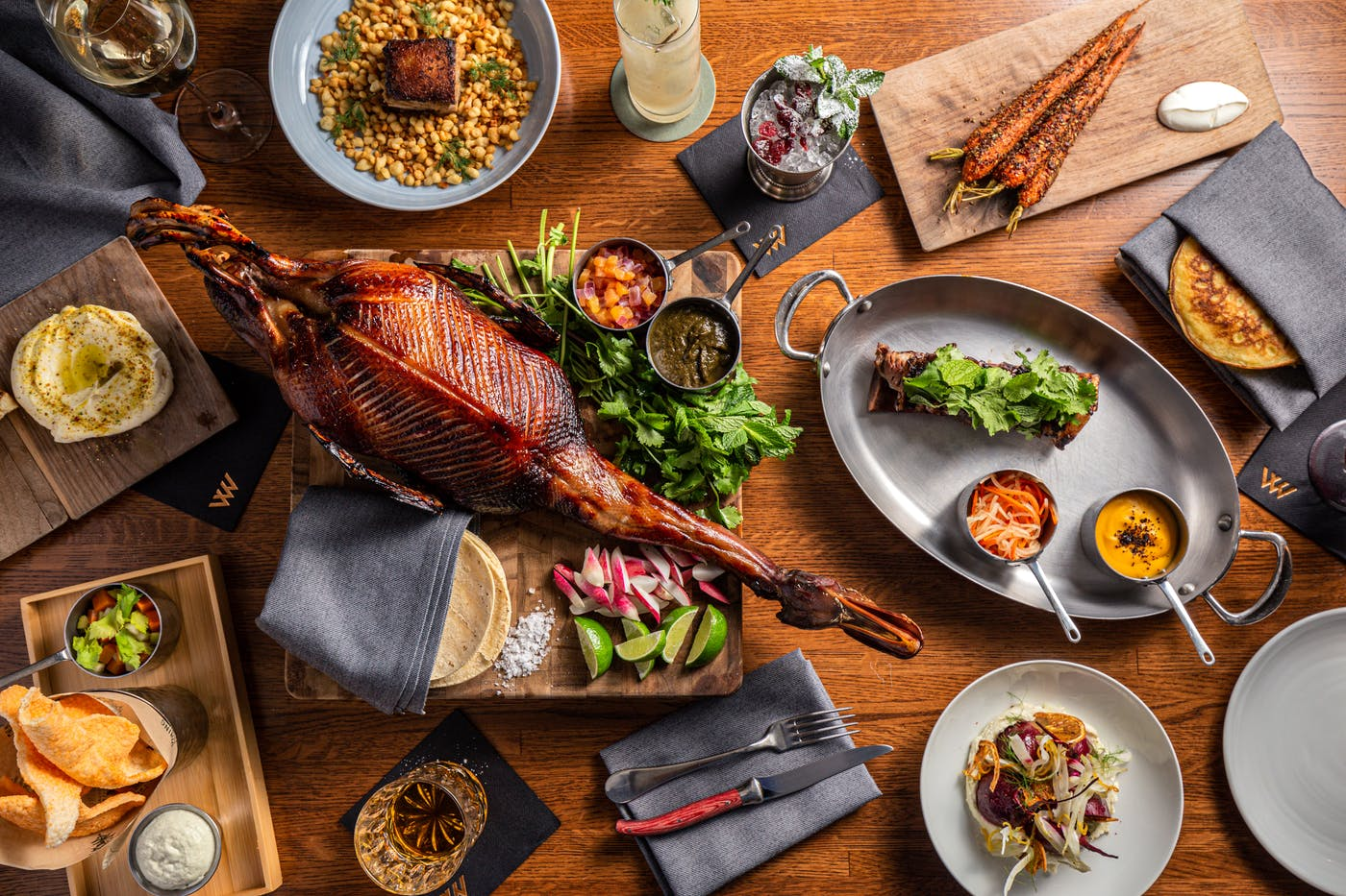 A spread of dishes on a table, including fire-roasted carrots, dry-aged duck, grilled short rib, and chicken chicharrónes.