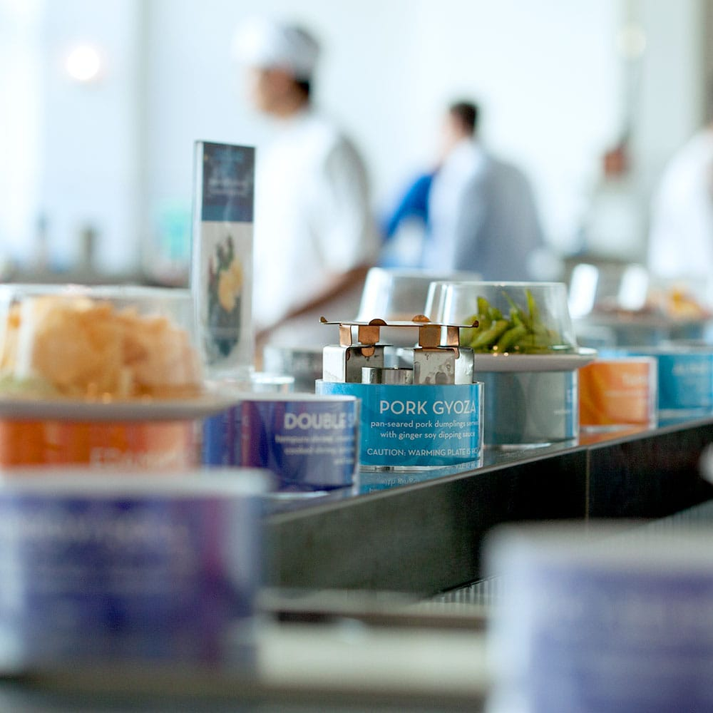 A view of the conveyor belt at Blue C Sushi, with edamame and pork gyoza displayed.