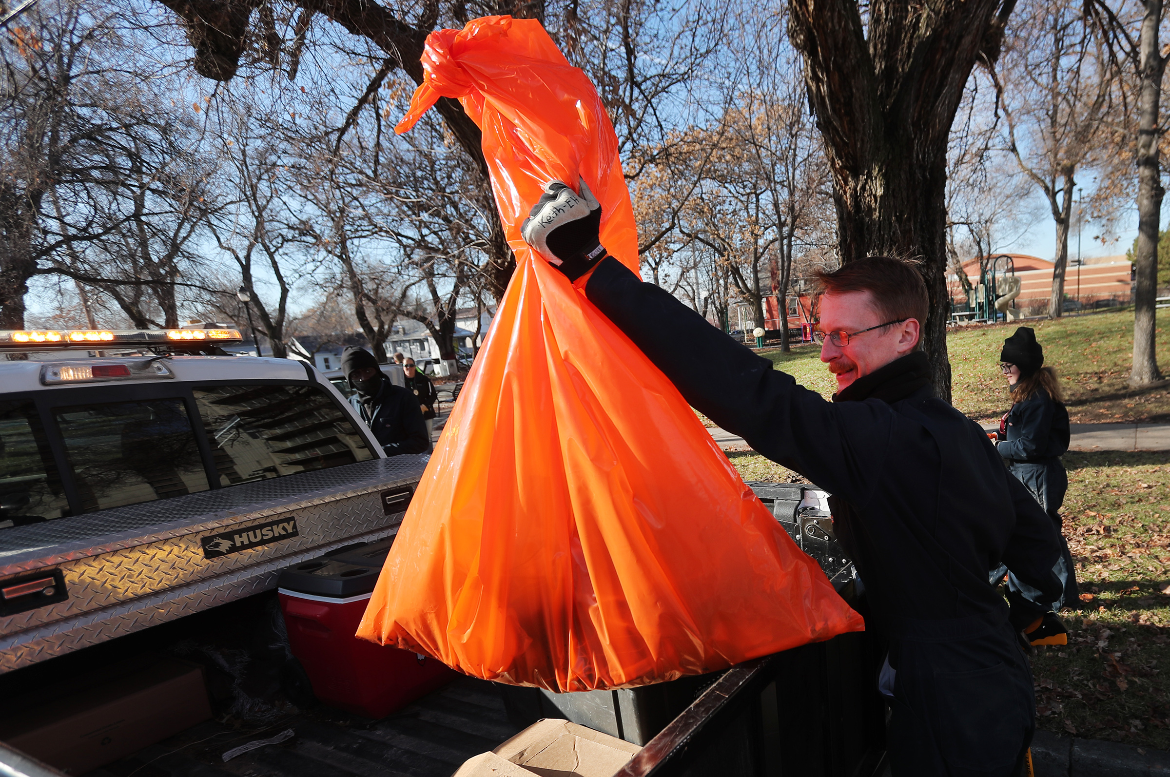 Keith Neijstrom, an environmental health technician, puts a bag of trash into the back of a truck as health department officials, Utah Highway Patrol troopers and Salt Lake City police officers clean up a homelss camp in Salt Lake City on Tuesday, Dec. 10, 2019.