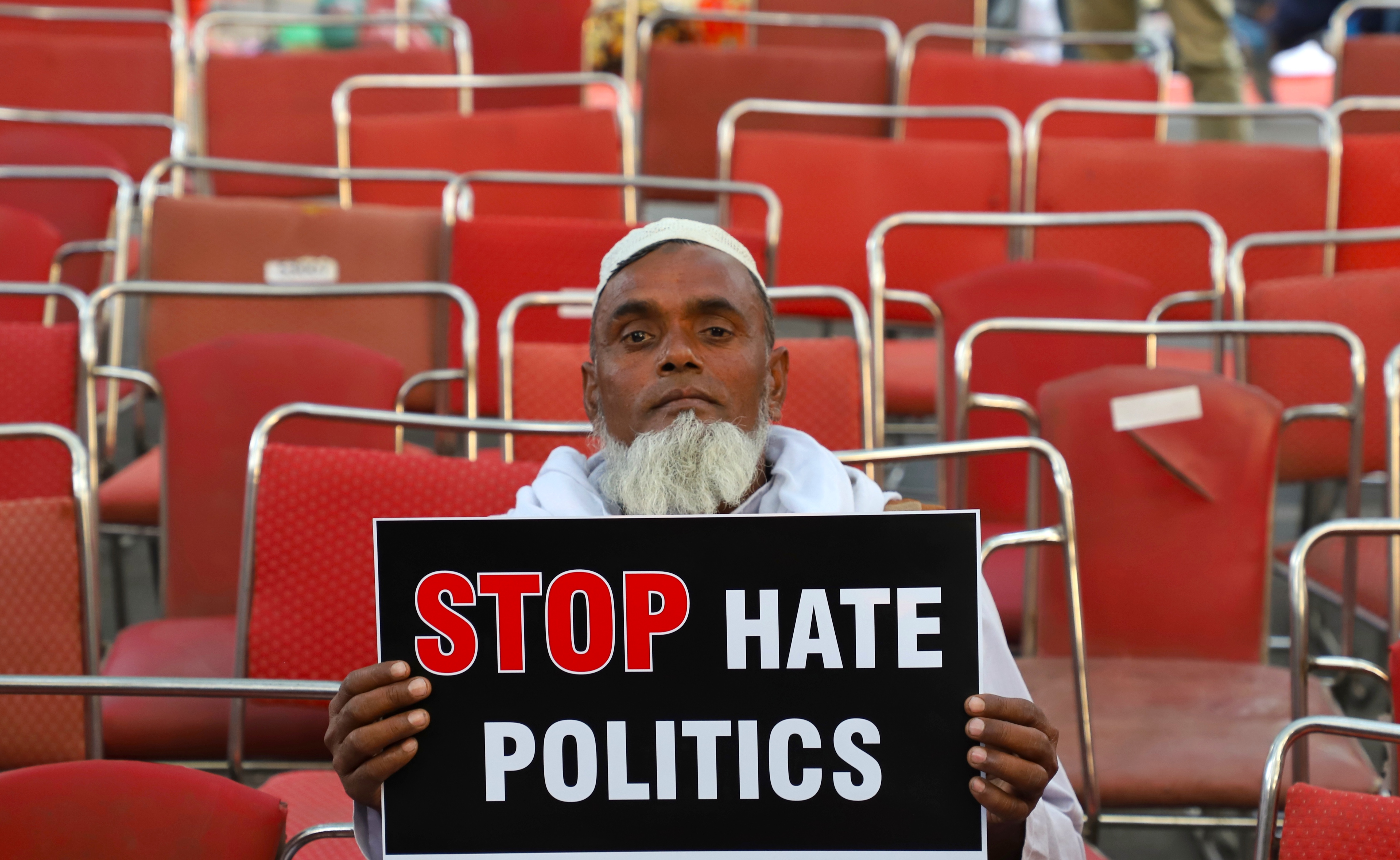 "An elderly man holds a placard saying ""Stop Hate Politics"" during a protest against the Citizenship Amendment Bill in New Delhi, India."