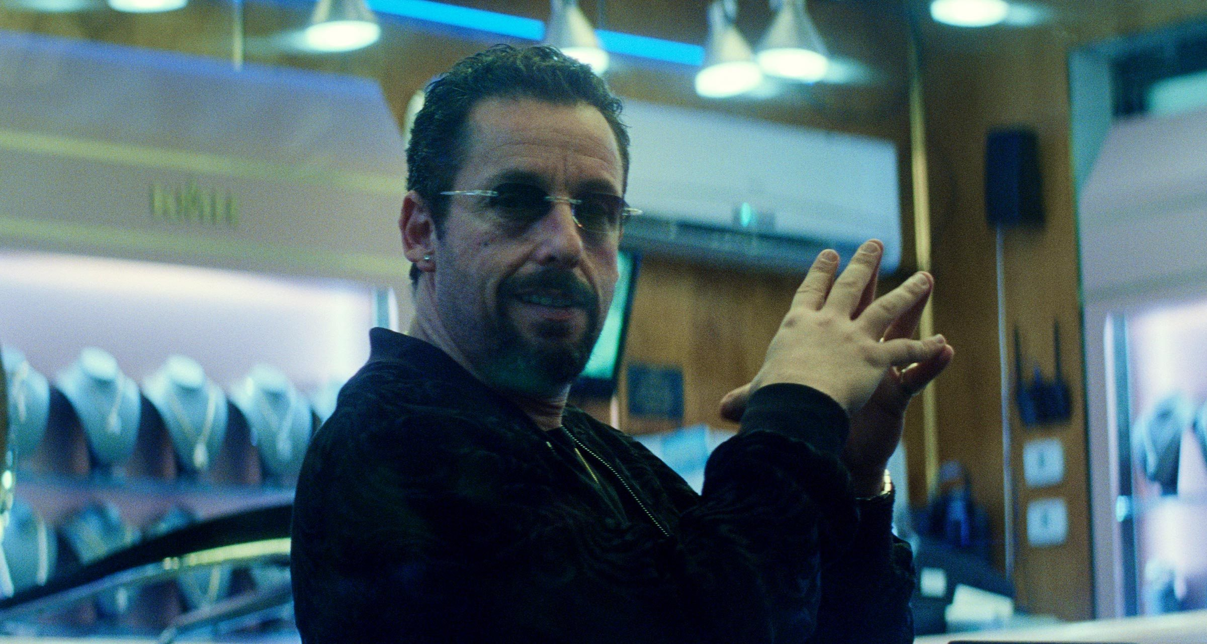 Adam Sandler, wearing dark glasses, tents his fingers in a shot from the movie Uncut Gems.