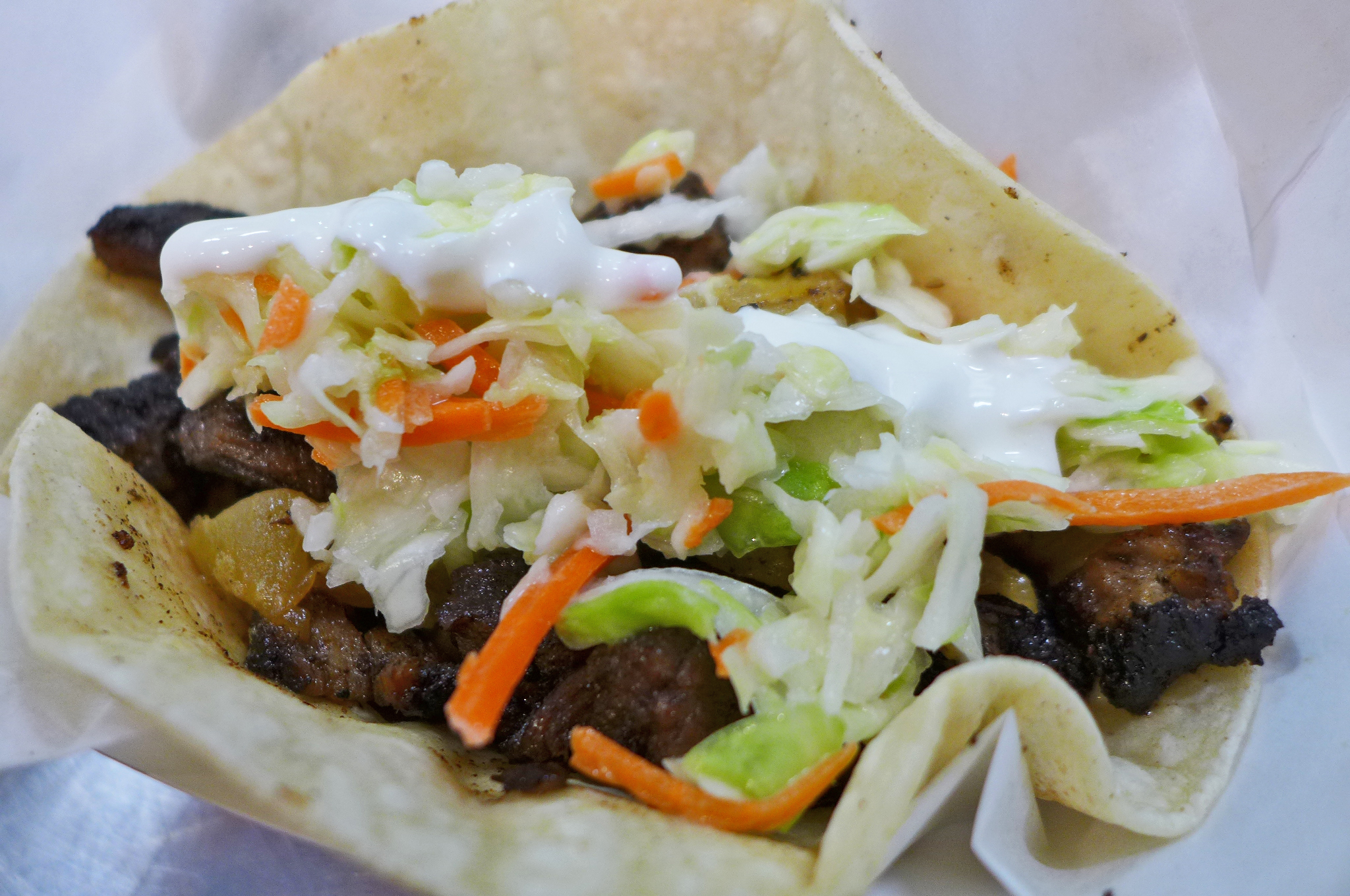 A soft corn tortilla holds dark chunks of meat, pineapple, pickled slaw, and bright white crema.