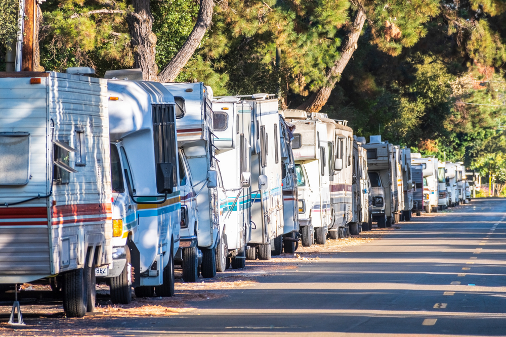 Campers and RVs parked extremely closely together on the side of a street.