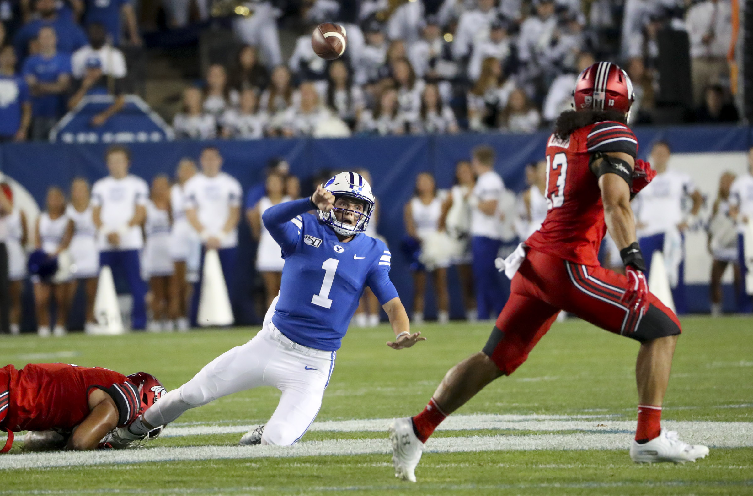 Brigham Young Cougars quarterback Zach Wilson (1) gets dragged down as he tries to throw a pass that is intercepted Utah Utes linebacker Francis Bernard, who ran it back for a touchdown during the University of Utah at BYU football game at LaVell Edwards Stadium in Provo on Thursday, Aug. 29, 2019
