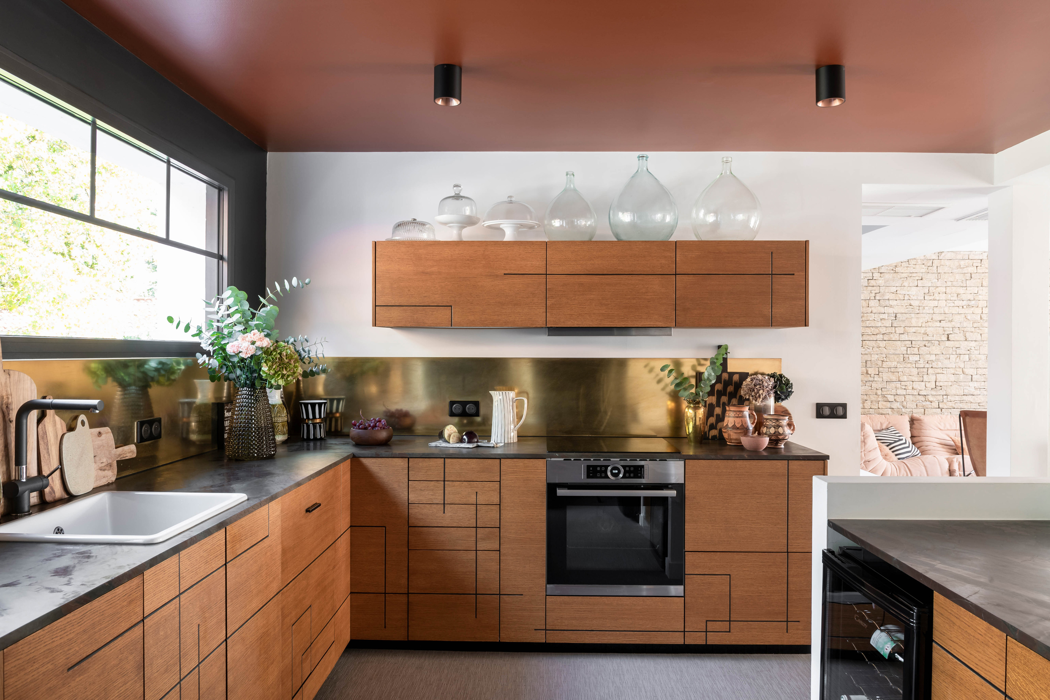 A modern kitchen with a clay colored ceiling.