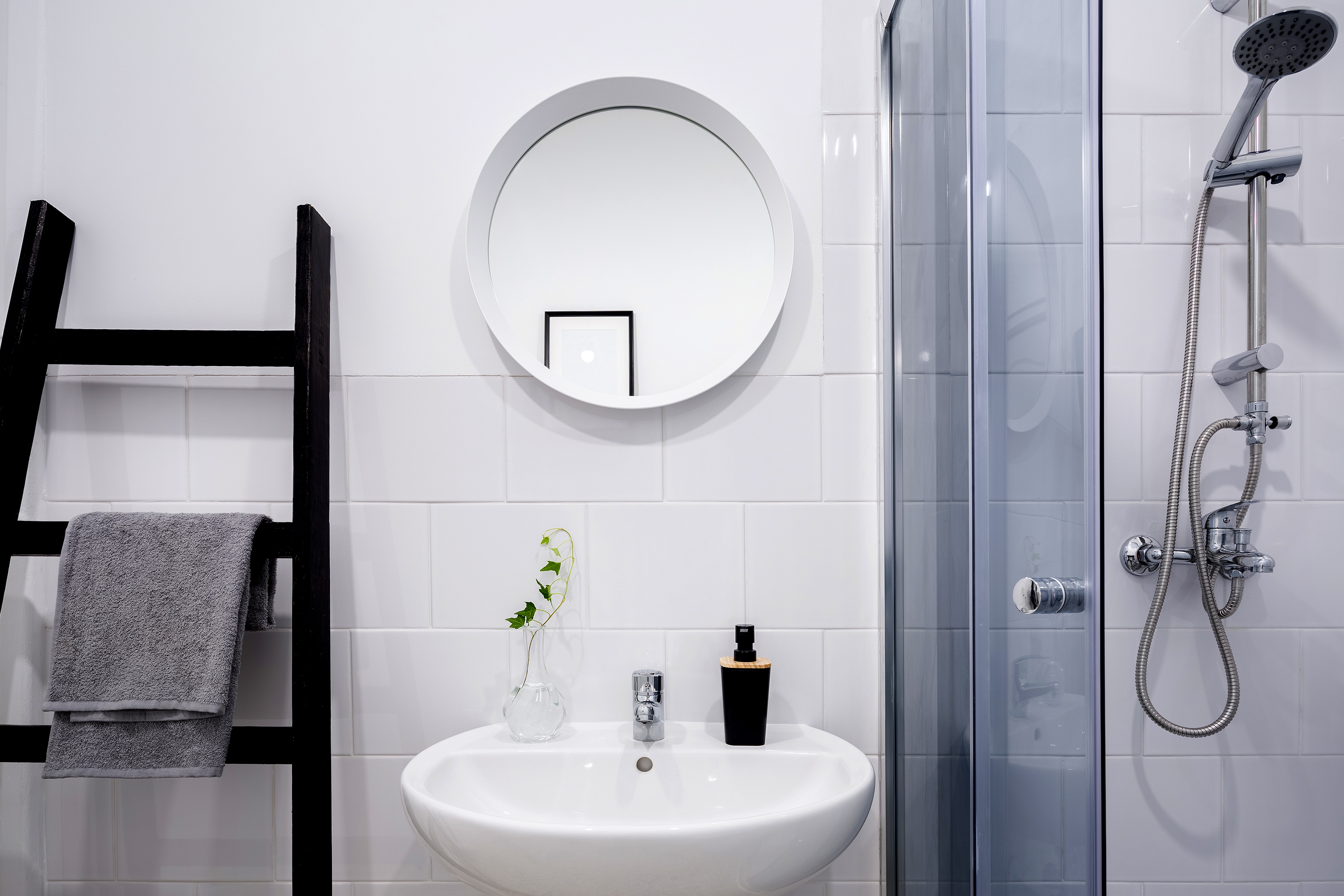 Small, bright bathroom with sink and shower.