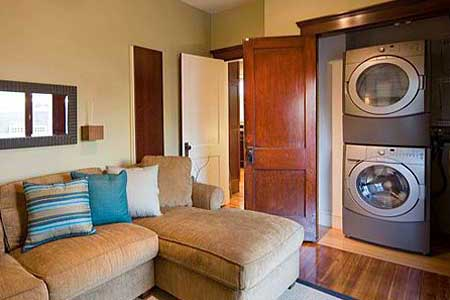A living room with a stacked washer dryer.