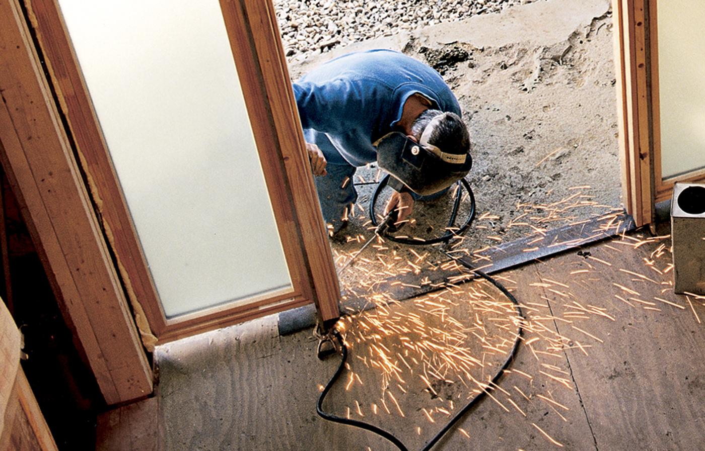 Man Welding Wooden Door Frame