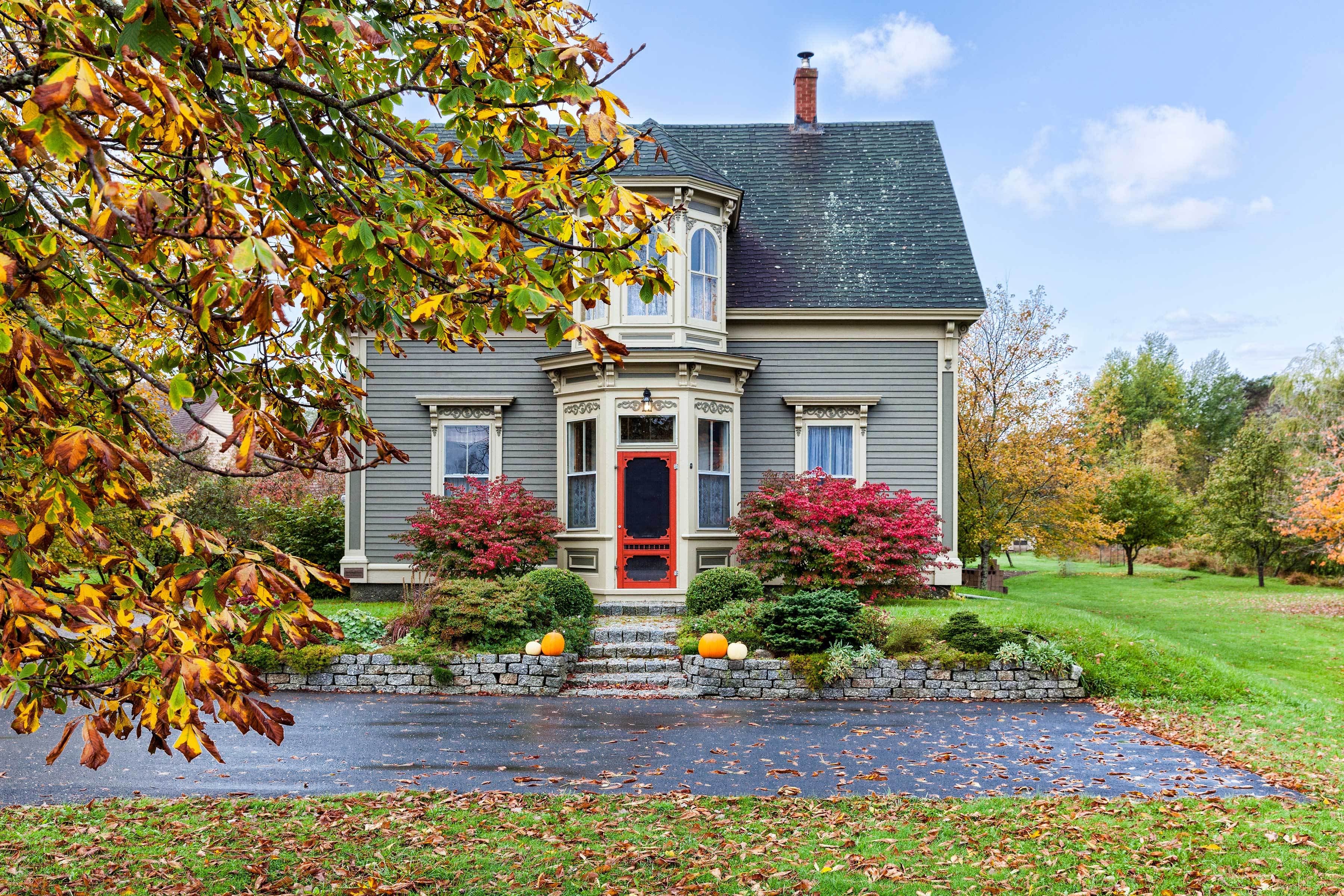 A gray house with victorian features in the fall.