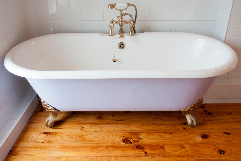 White clawfoot tub on hardwood floor.