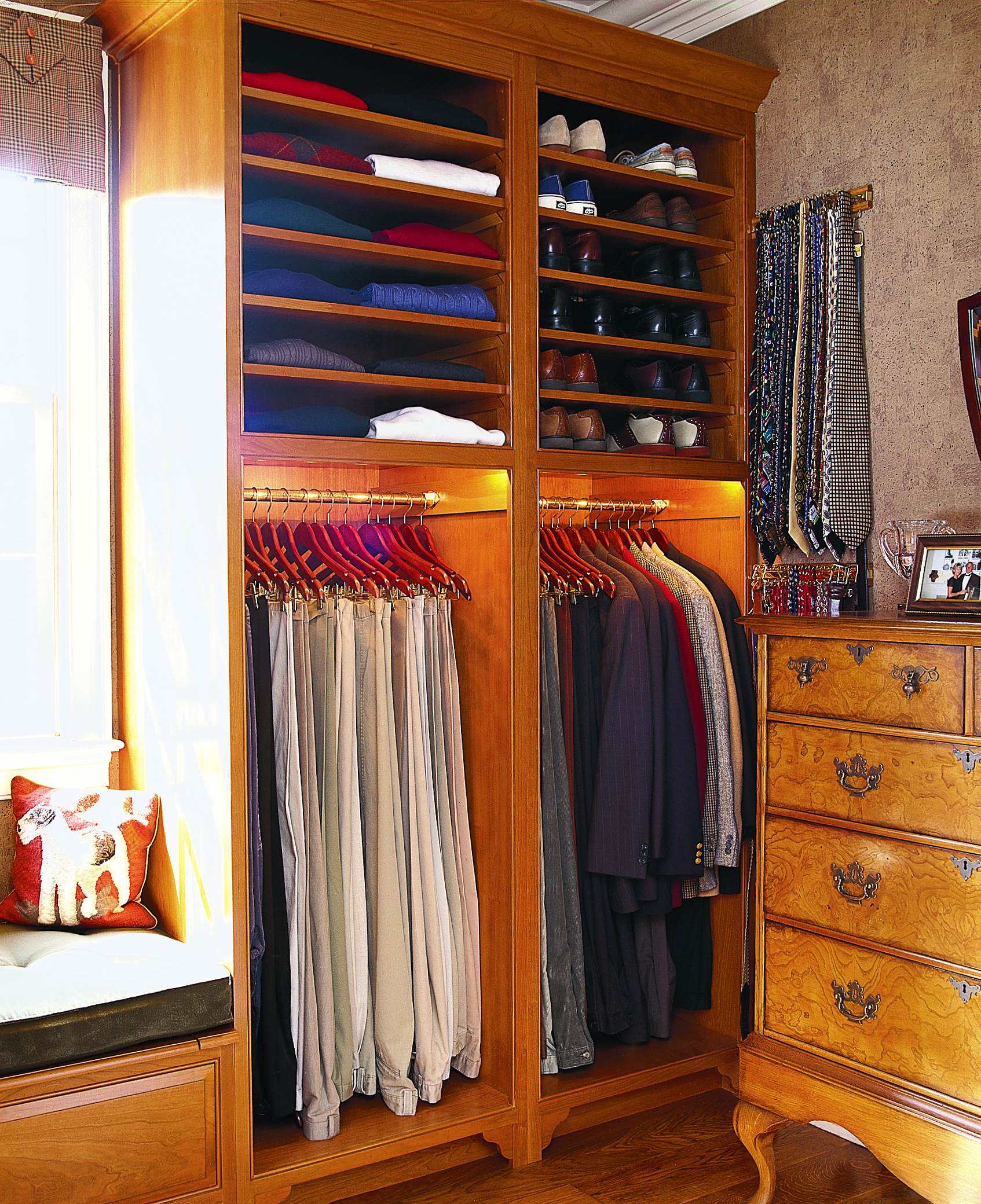 A closet design that has two hanging sections and then shelves above it for shoes and folded clothes.