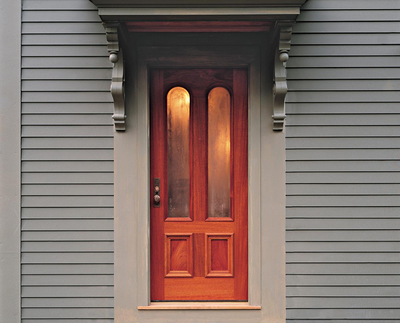 Wooden front door nestled between two grey corbels.