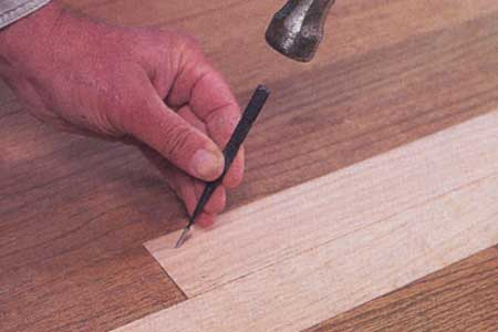 Man Patches Hardwood Floor