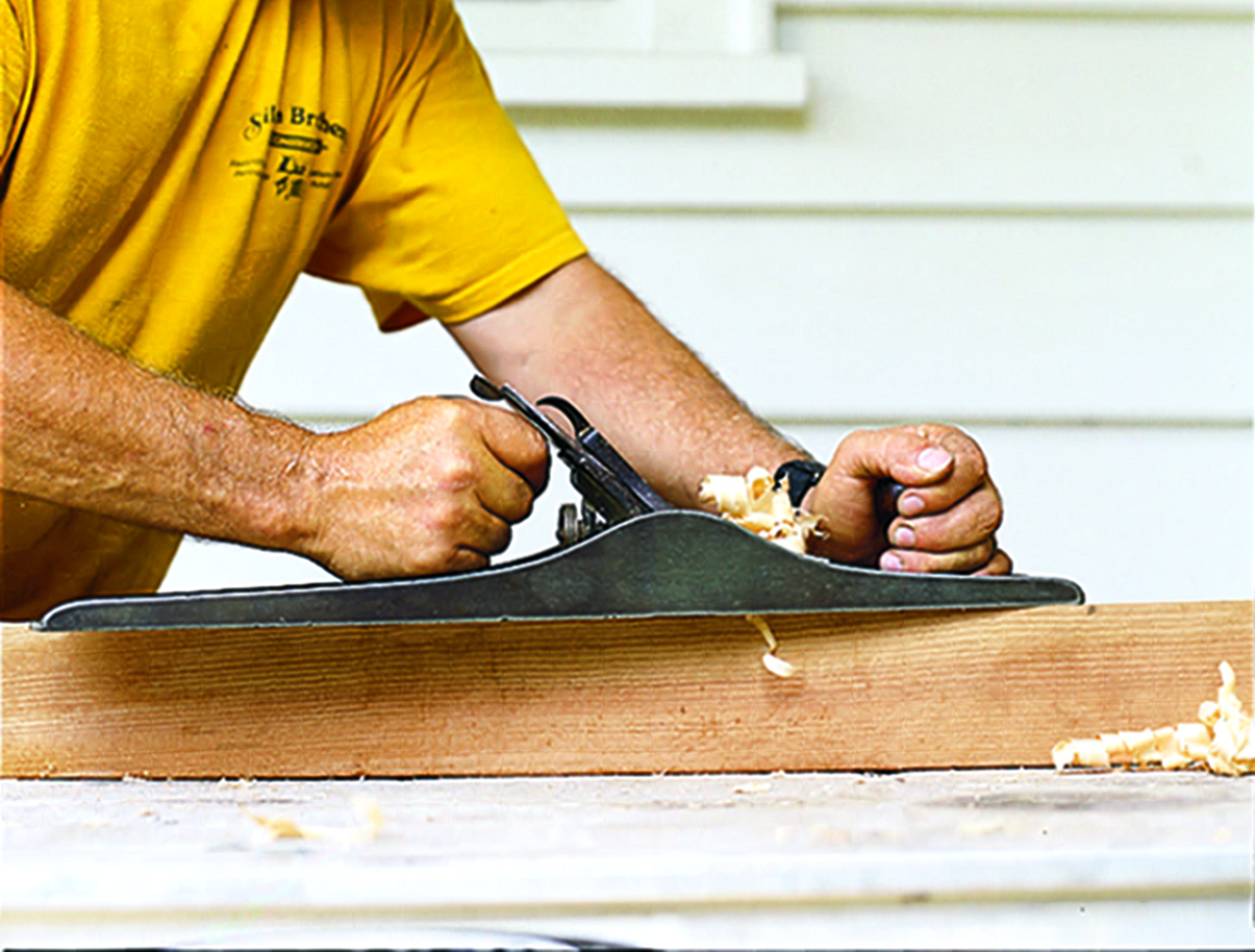 Person using a hand planer on wood.