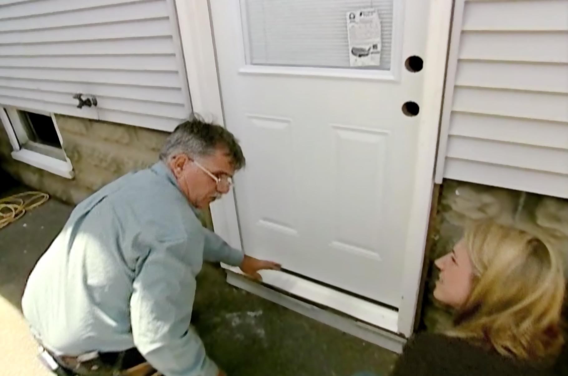 People blocking drafty door with long tubes.