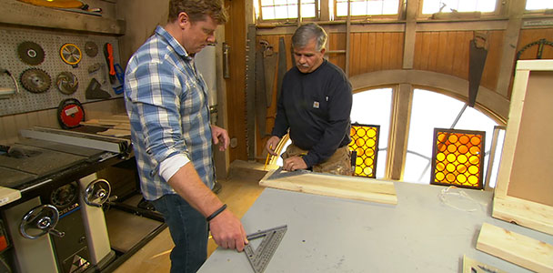 Two people demonstrating how to use a speed square to measure and cut a 2x4.