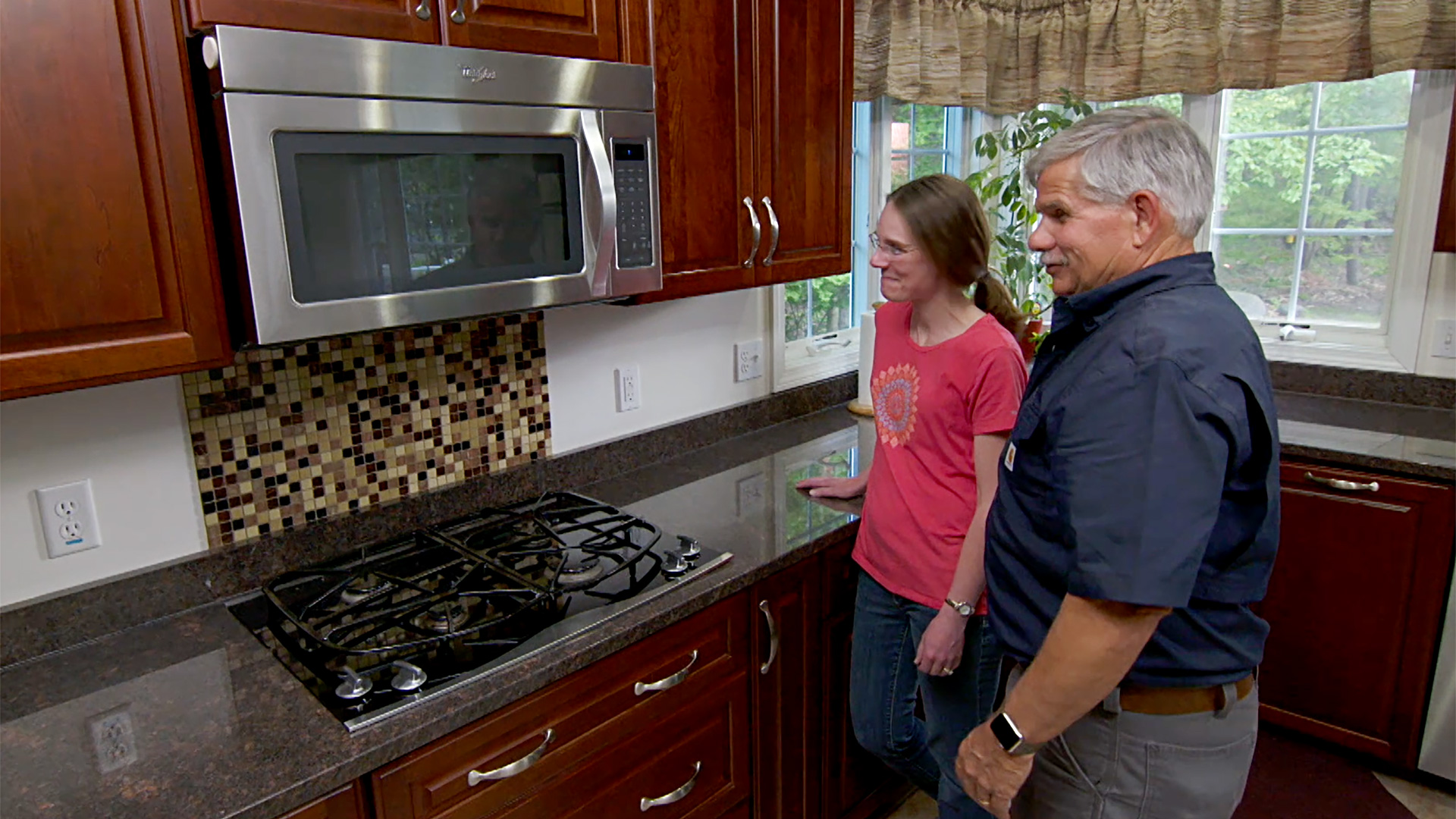 Two people looking at a newly installed tile backsplash.