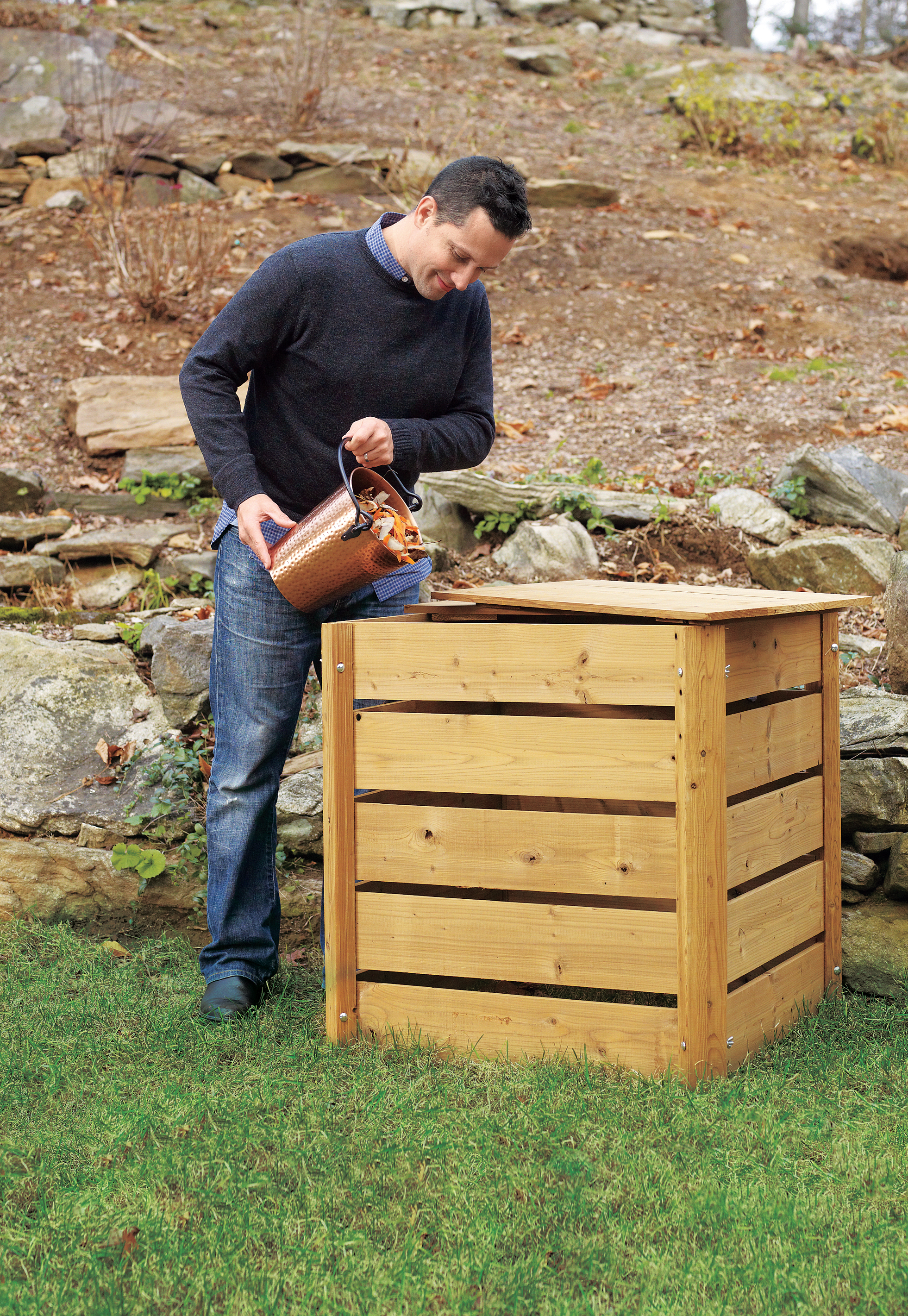 Man Dumps Material From Compost Pail Into Wooden Compost Bin