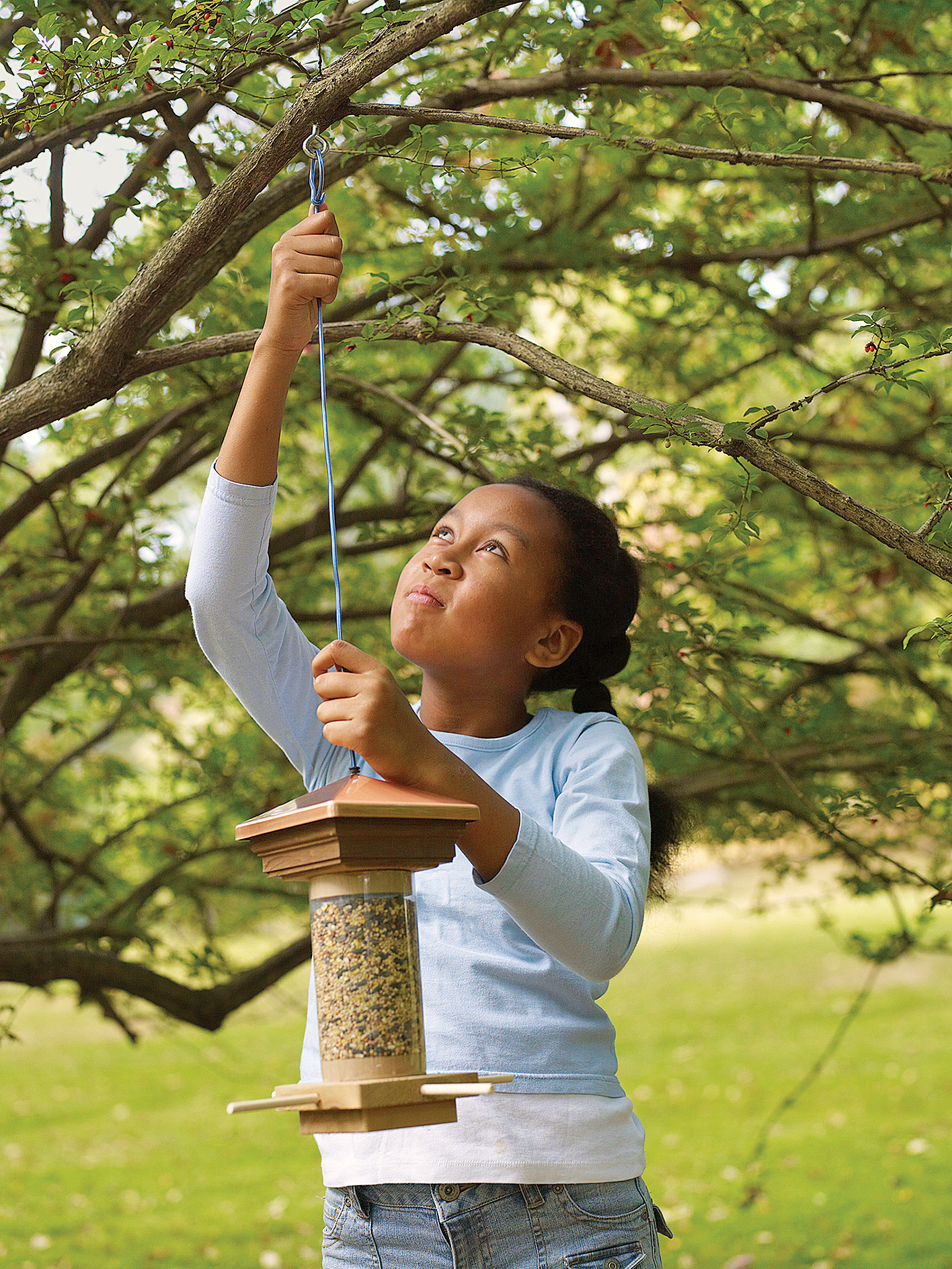 Kid handing up a DIY bird feeder.