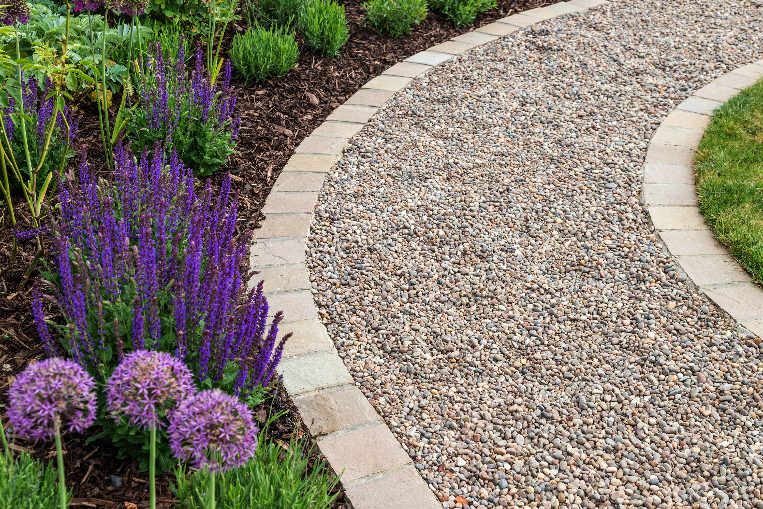 Gravel path lined with flowers.