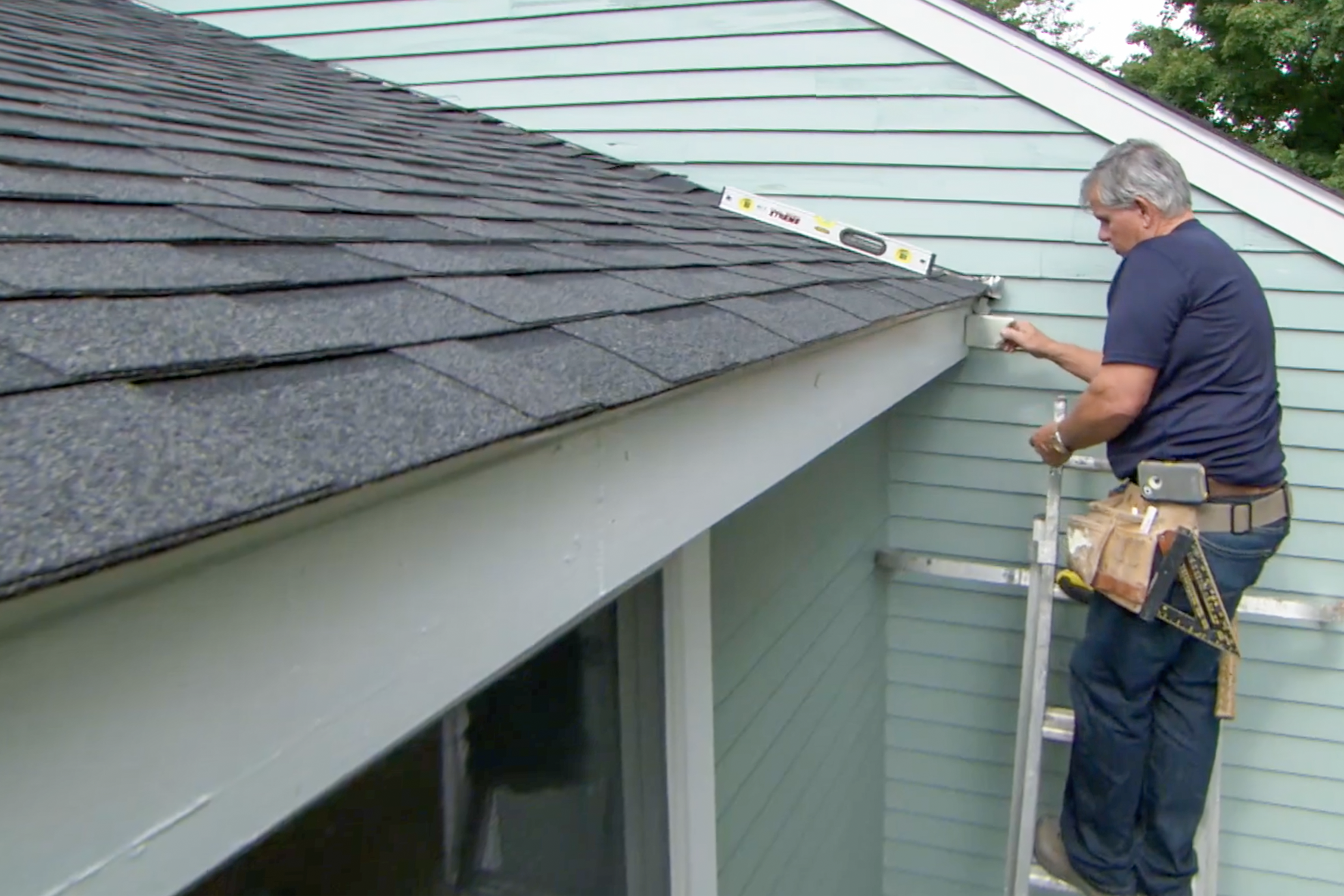 Tom Silva measuring a roof to install new gutters.