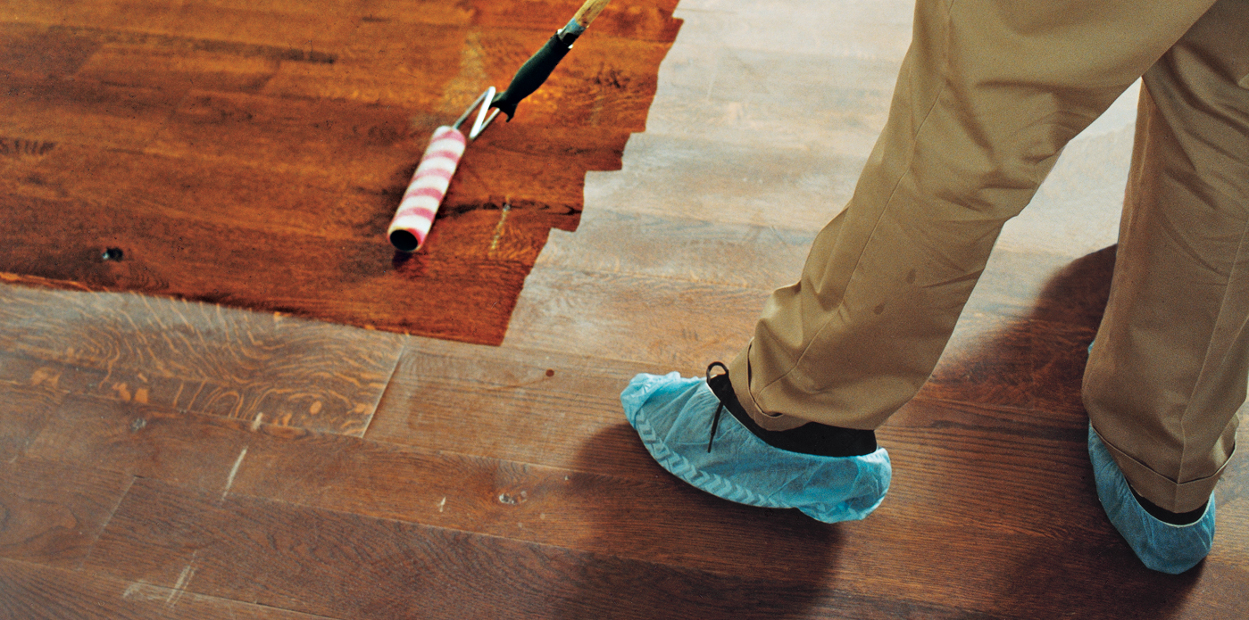 Person Applying Polyurethane On Hardwood Floor