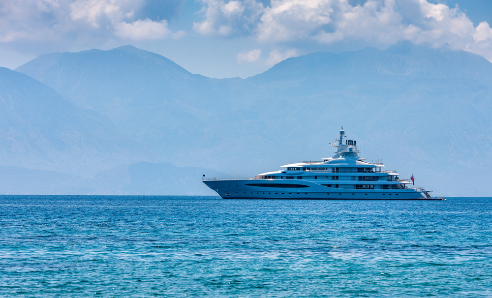 A large luxury white yachtfloating in a blue sea.