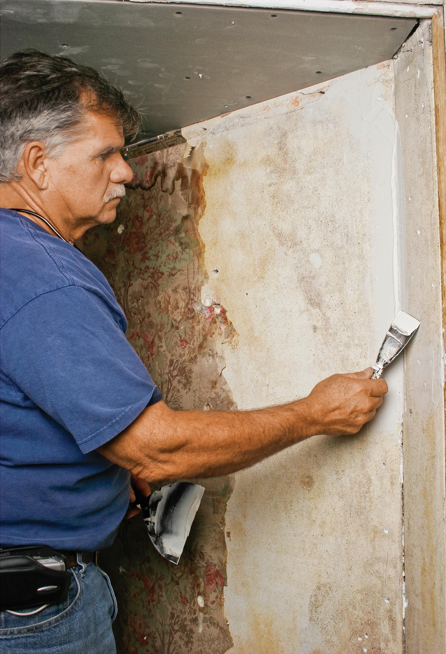 Man Repairs Crack in Plaster Wall