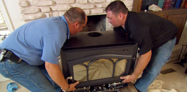 People carrying a wood stove insert to install it into a fireplace.