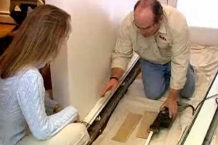 Person removing baseboard heater covers.