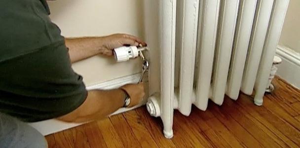 Person installing thermostatic steam radiator valve.