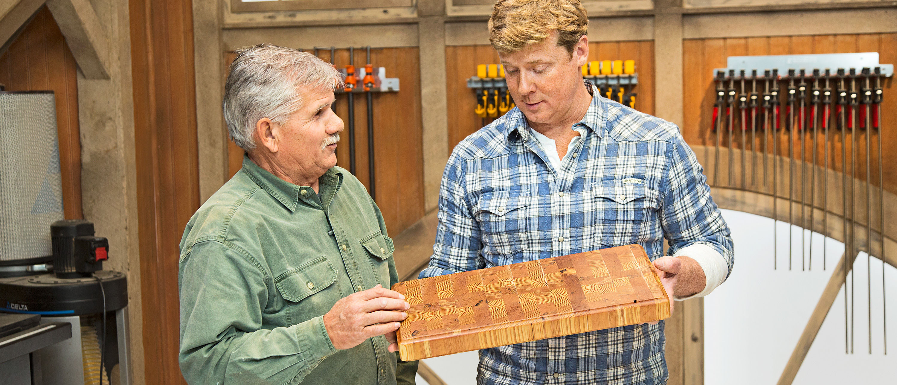 Two people holding an end grain cutting board made from scrap wood.