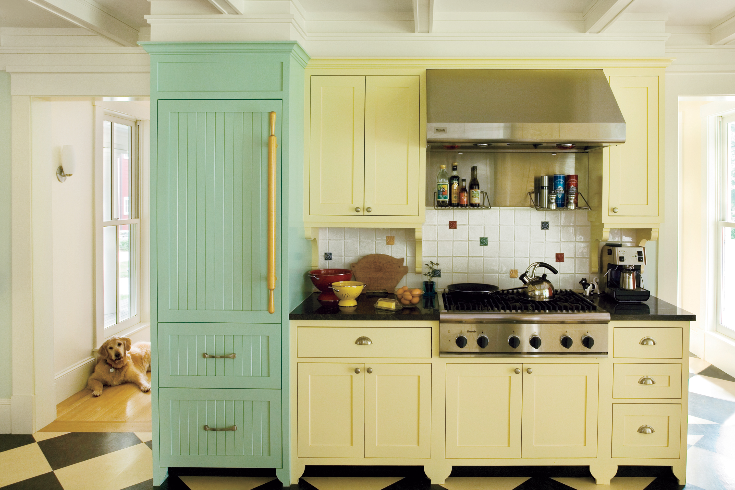 Tall green cupboard next to soft yellow kitchen cabinet and drawers.