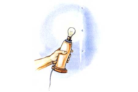 A lamp with a bare bulb held against a wall used to locate studs.