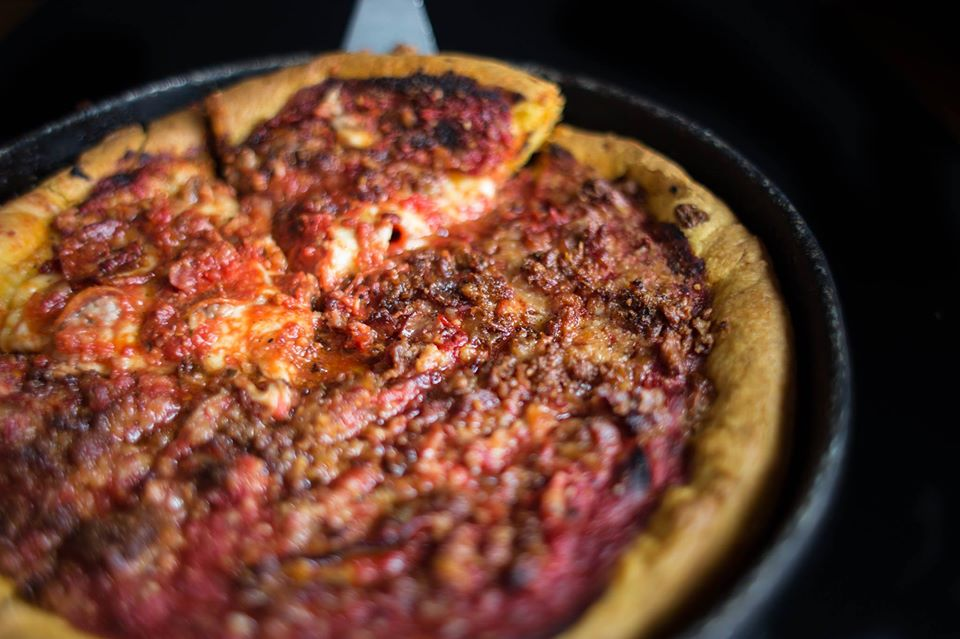 Deep dish pizza with a slice being pulled out.