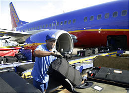 Ramp agent Arthur Wiley unloads a Southwest Airlines' aircraft in Dallas. Southwest has maintained 57 straight profitable quarters.