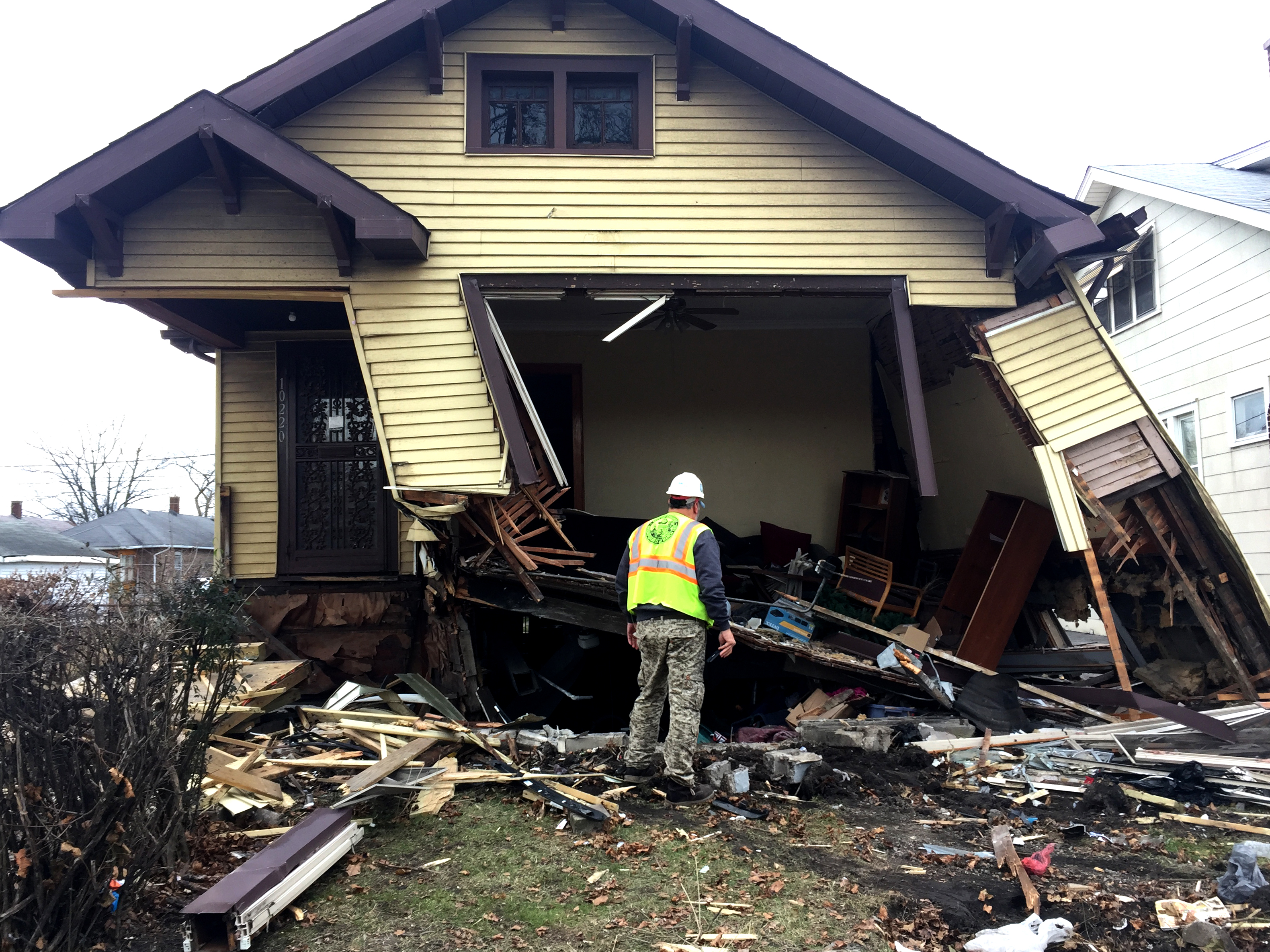 A worker with the city's Streets and Sanitation Department inspects a home at 102nd Street and Wentworth Avenue after a vehicle crashed into it Thursday, leaving one person dead and two children hospitalized.