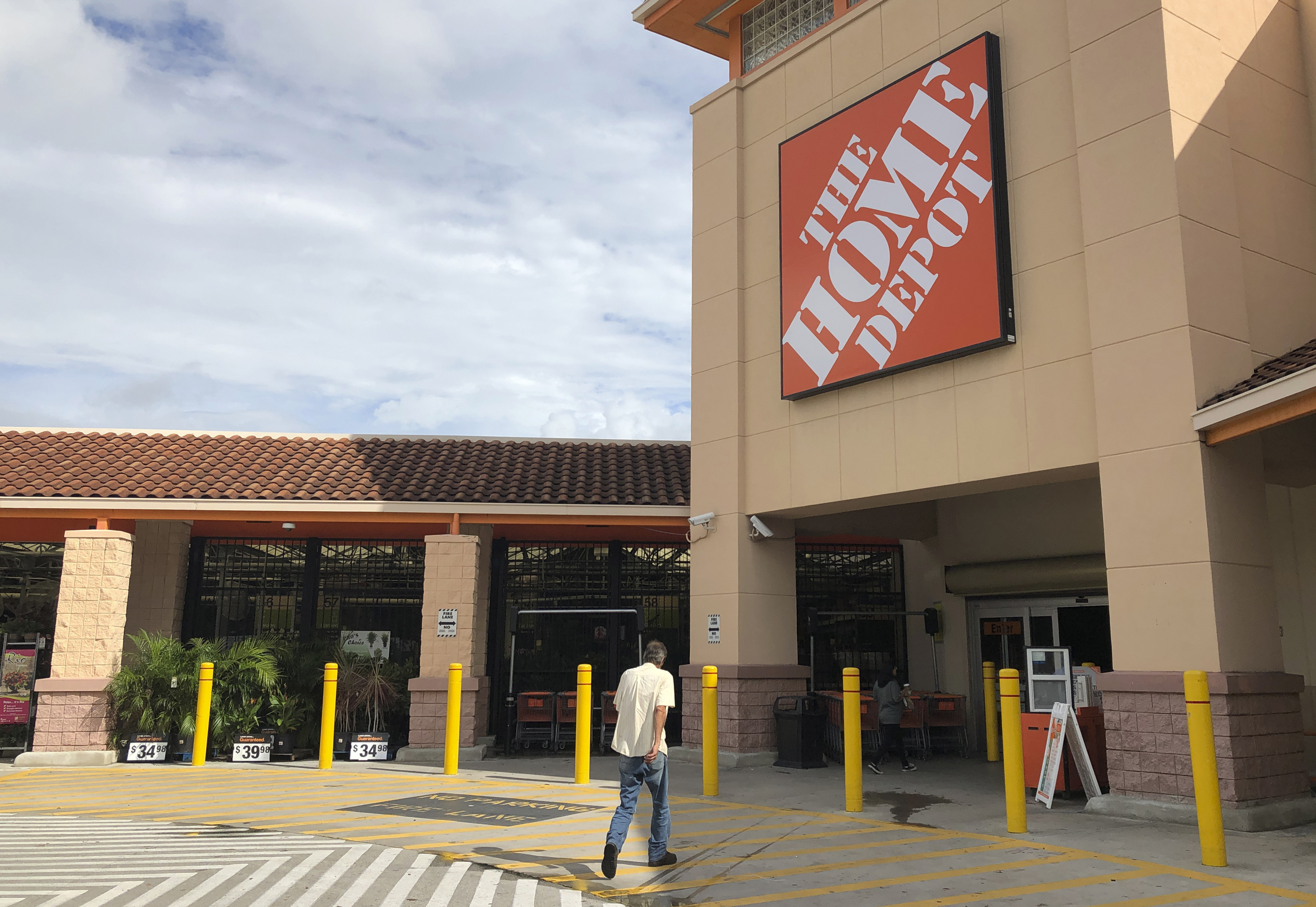 In this Monday, Oct. 7, 2019 photo, a customer enters The Home Depot store in Miami. (AP Photo/Wilfredo Lee)