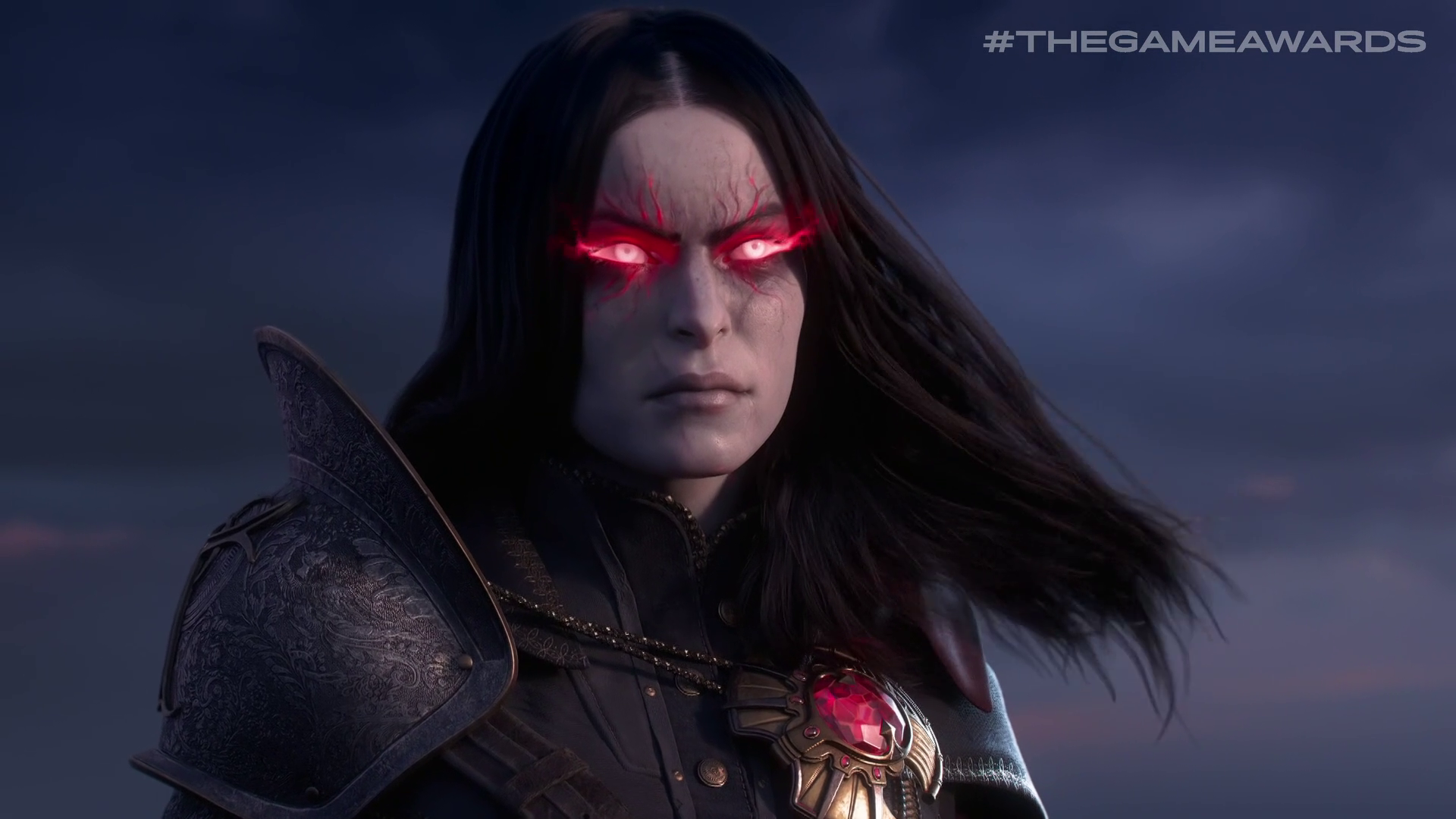 a dark-haired woman with flaming red eyes and a red jewel in New World