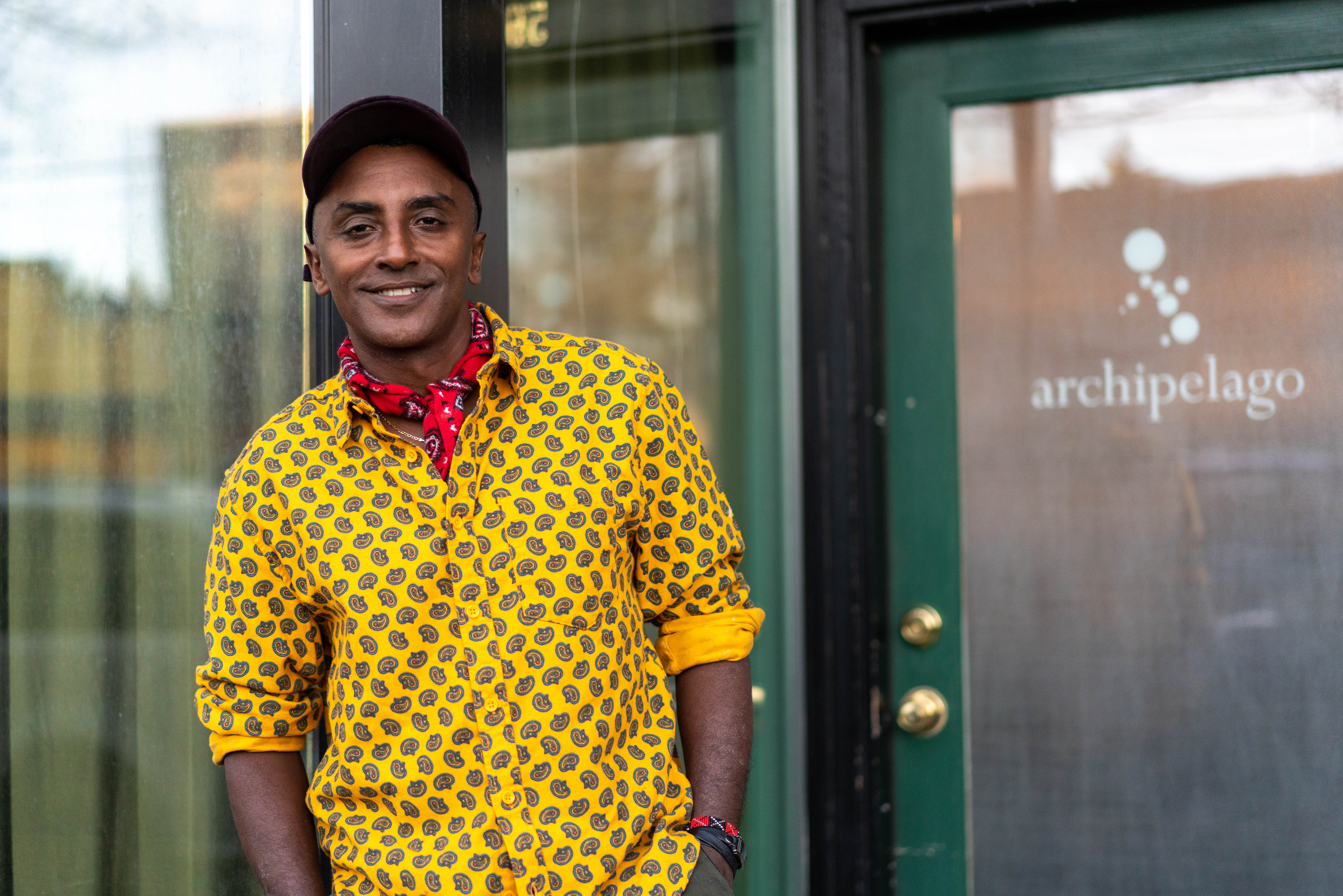 Host Marcus Samuelsson standing in front of Seattle restaurant Archipelago, which is featured in the show.