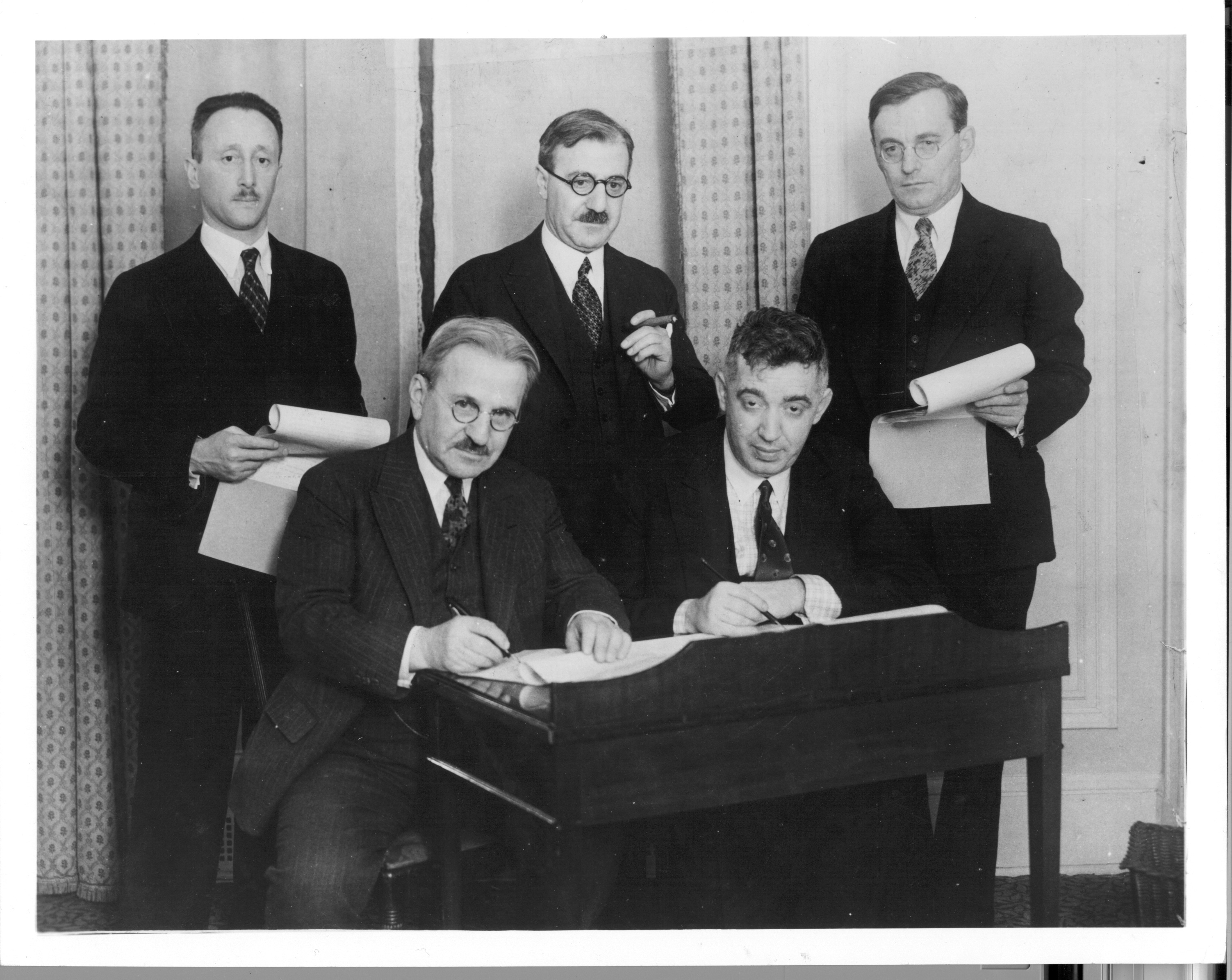 An old black and white photograph of five men, two sitting, with one signing a document.