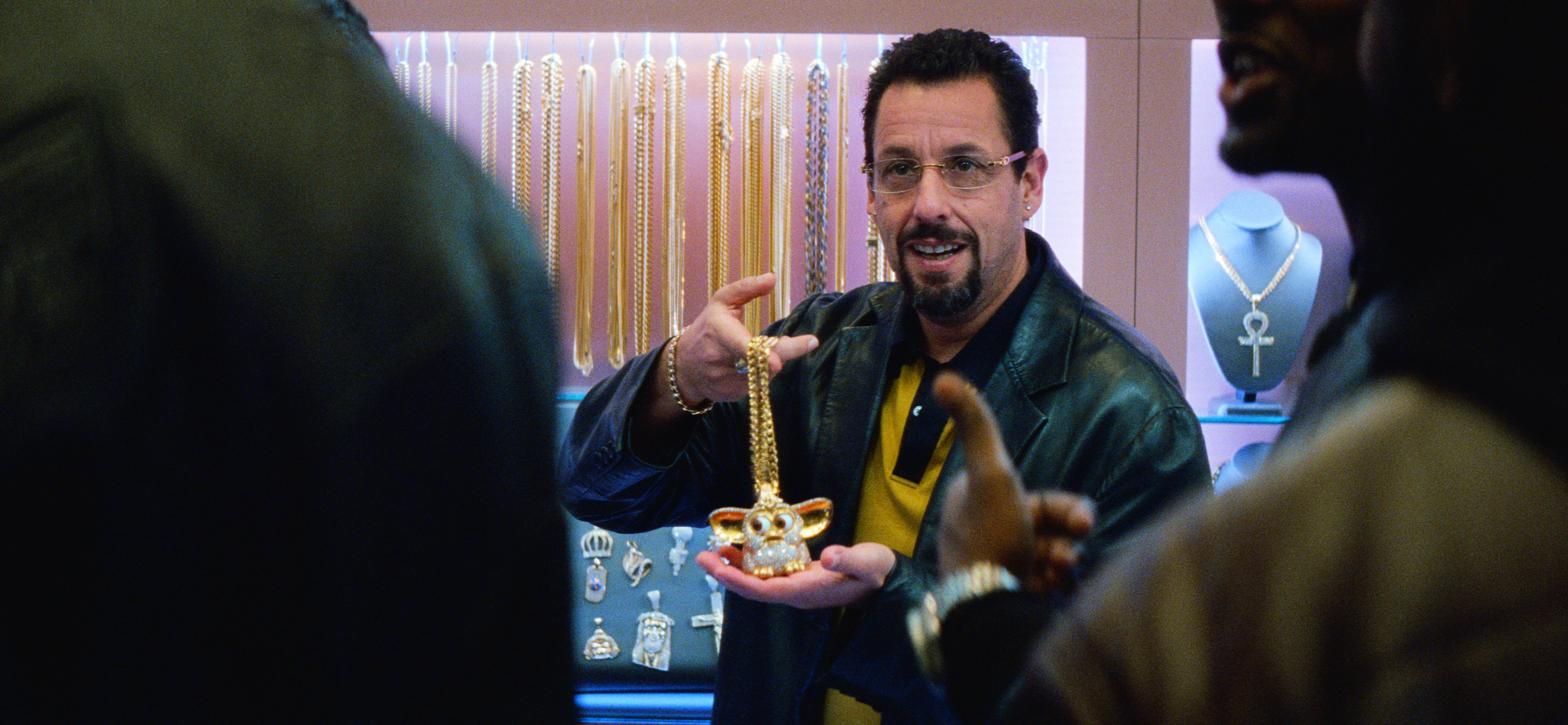 Howard Ratner (Adam Sandler) holds up a diamond-encrusted Furby necklace