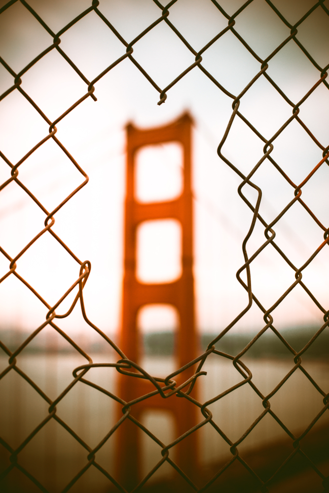 An orange-painted tower of a suspension bridge, seen through a whole in a chainlink fence.