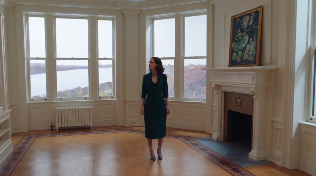 A woman stands in a bright living room with windows overlooking a river.
