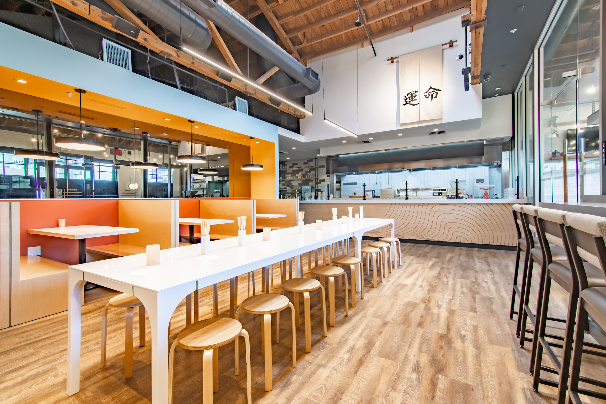 A brightly colored Japanese fast casual restaurant, with lots of wood and orange tones.