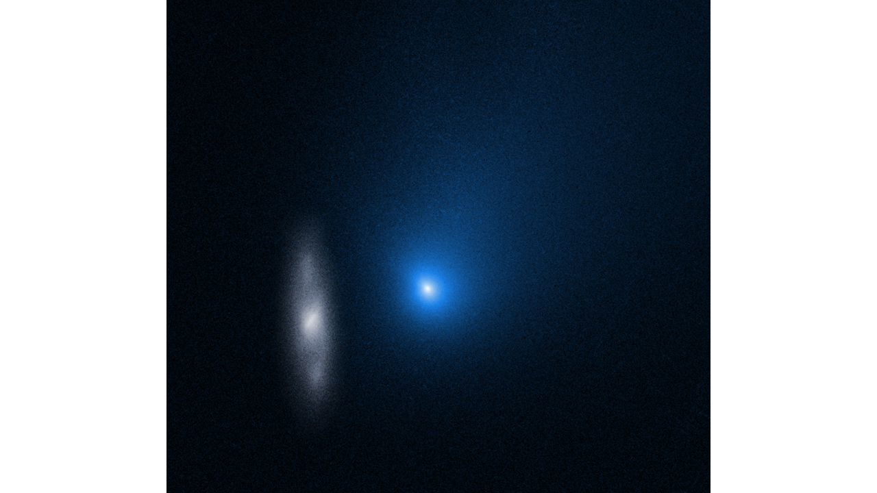 The comet appears as a glowing blue dot in this hubble space telescope image. To the left of it, is a spiral galaxy.