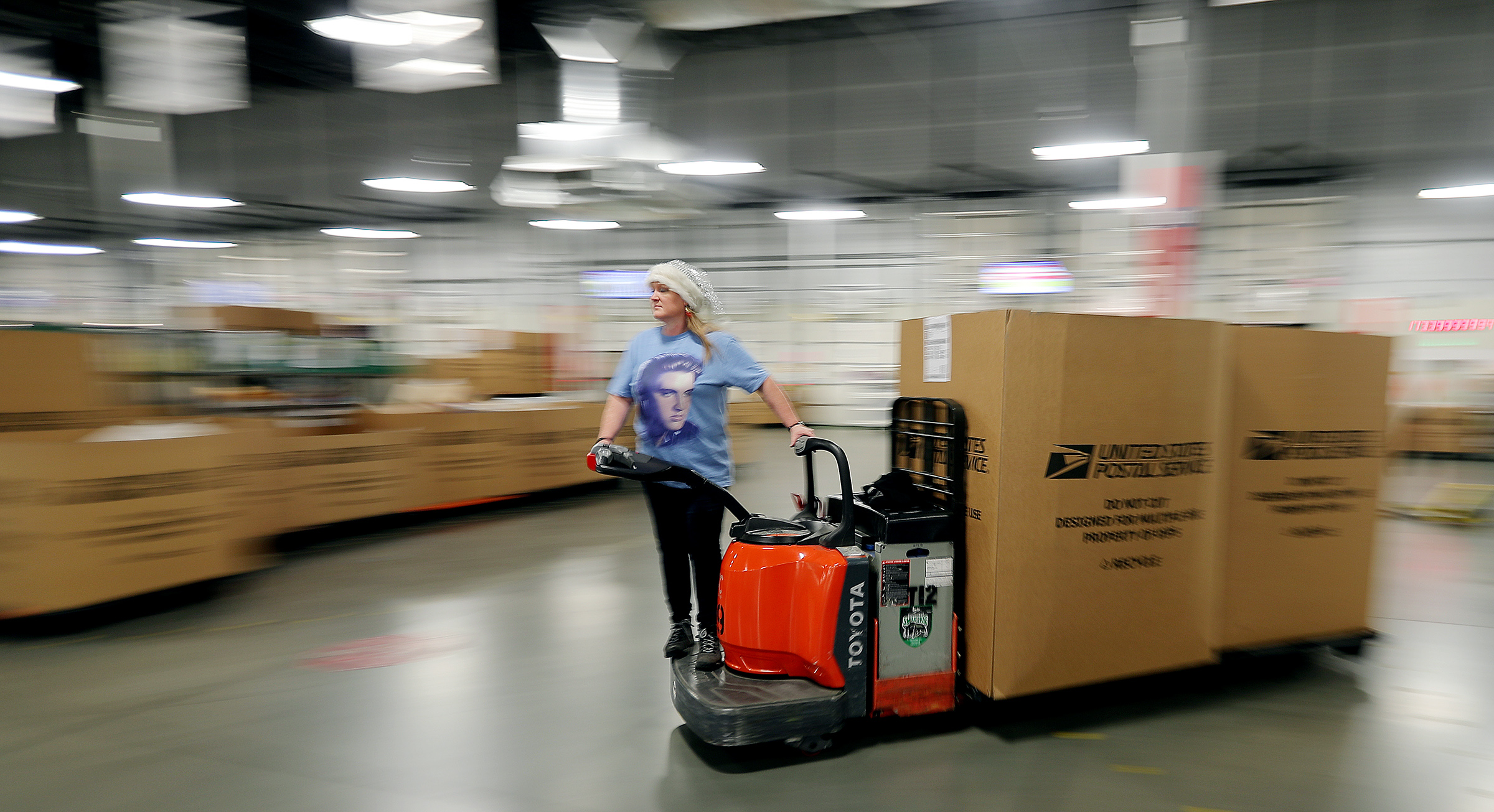 Mail handler Yvette Allgood, moves boxes of mail as United States Postal Service workers sort mail at a processing facility in Salt Lake City on Wednesday, Dec. 11, 2019.