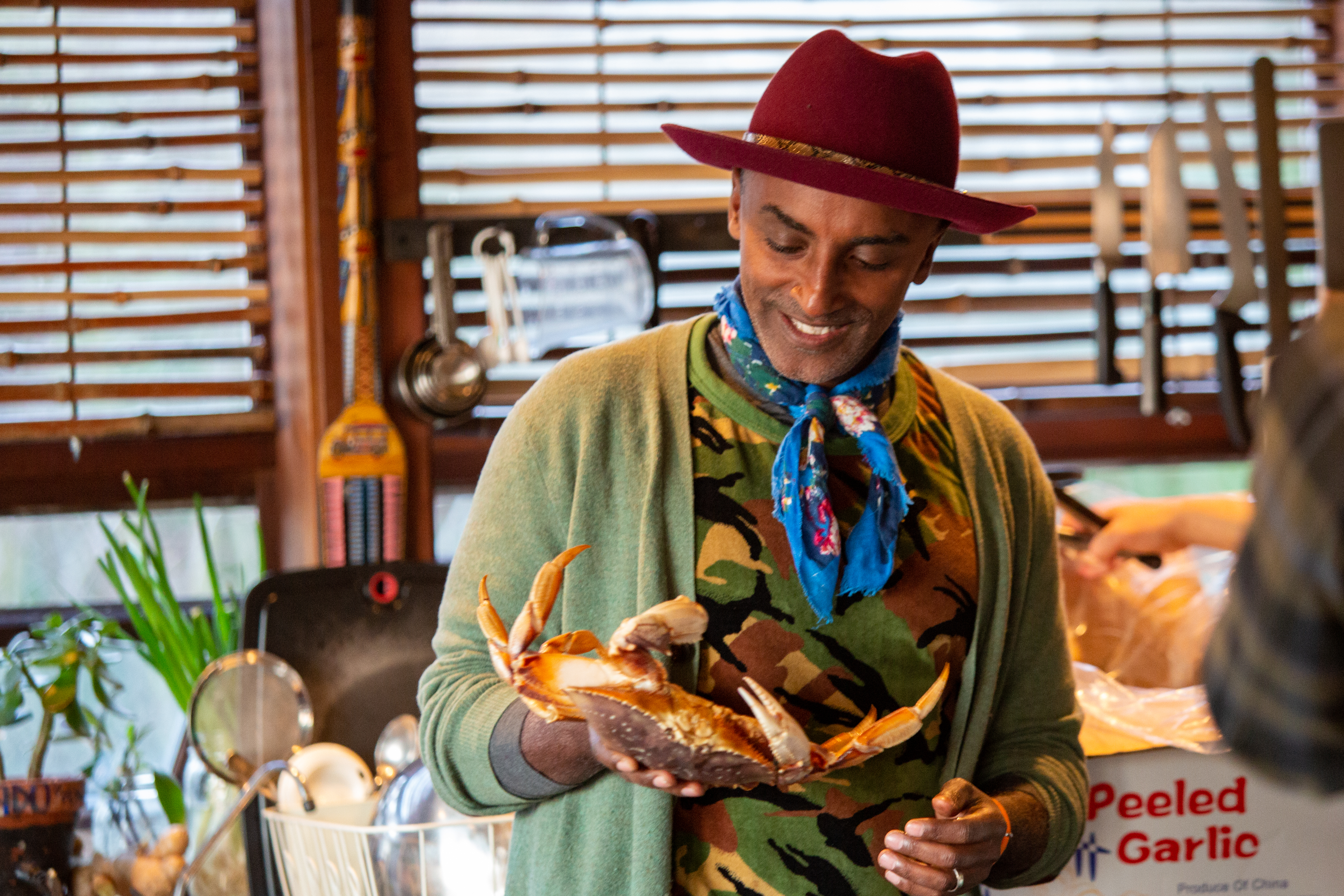 Host Marcus Samuelsson holding a crab in a home kitchen for the Seattle episode of No Passport Required.
